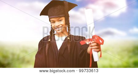 Cute pupil in graduation robe against sunny landscape