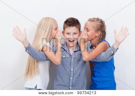 Teenage girsl whispering in the ears of a secret teen boy on white  background