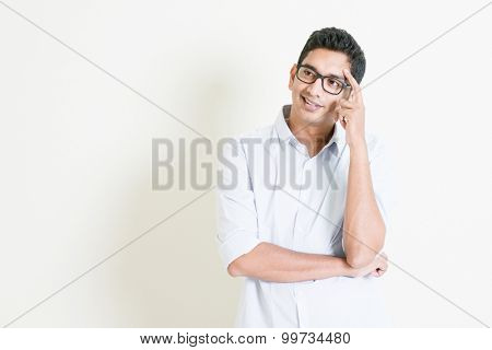 Portrait of handsome casual business Indian man having a thought and smiling, eyes looking upwards, standing on plain background with shadow, copy space at side.