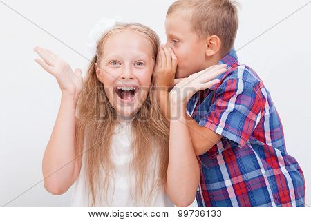 Teenage boy whispering in the ear a secret to teen girl on white  background