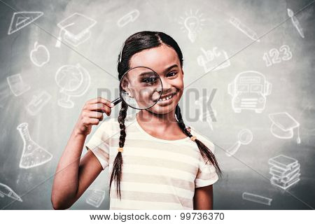 Education doodles against little girl holding magnifying glass in classroom