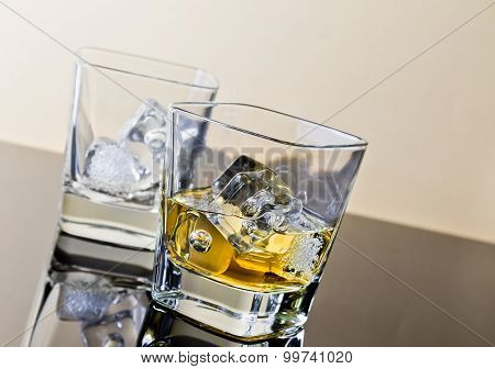 One Glass Of Whiskey And One Empty With Ice Cubes On Black Table With Reflection