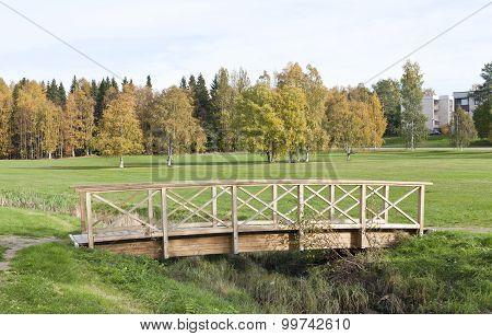 Wooden and modern bridge above a brook, creek.