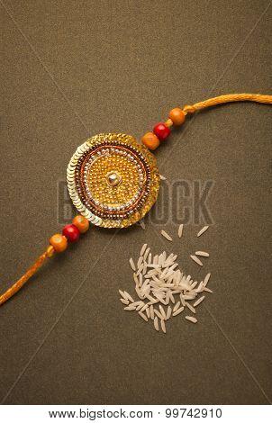 Handmade golden Rakhi with scattered white rice grains.