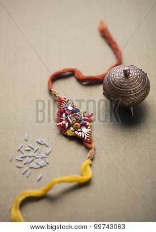 A Rakhi with rice grains and kumkum holder. An idian festive background.