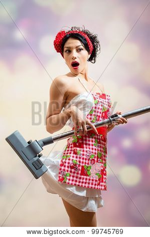 Surprised funny girl with hoover sucking in her dress