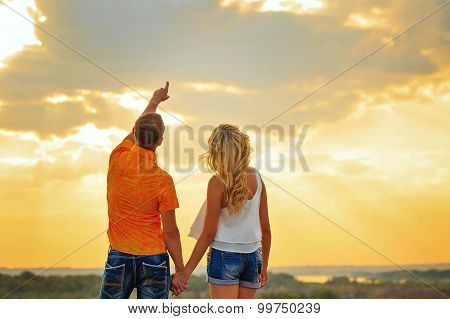 Loving Couple Looking At The Sky At Sunset.