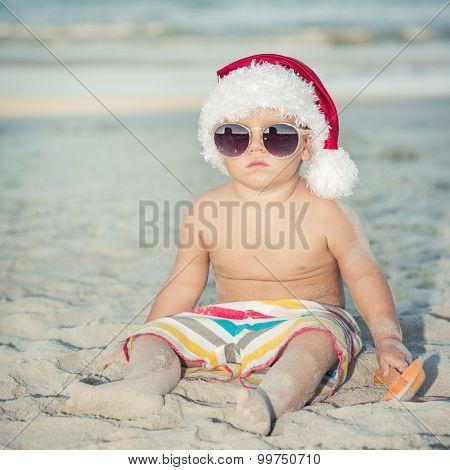 Cute baby wearing Santa hat on the beach