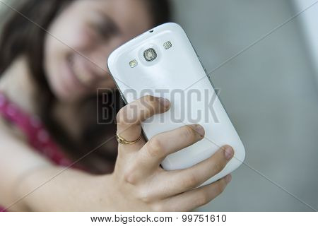 Teenage girl taking a selfie with her phone. Focus on smart phone