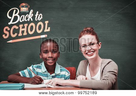 Happy pupil and teacher against green chalkboard
