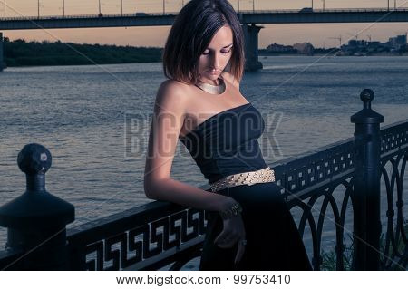 Women in deep sorrow leaning against fence in twilight time.