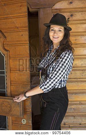 Woman In Lederhosen Standing At A Door