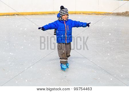 cute little boy learning to skate in winter