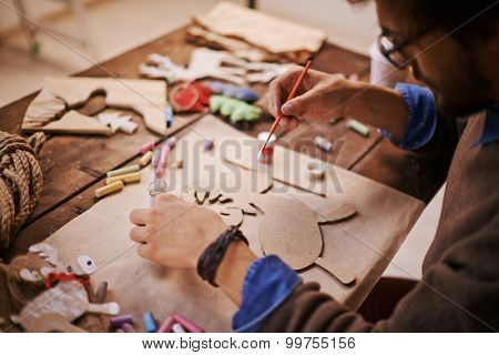 Craftsman with paintbrush painting paper deer before Christmas