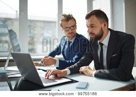Serious employee browsing on laptop while his co-worker pointing at its display