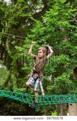 Boy climbing in adventure rope park in safety equipment