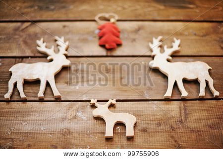 Three wooden xmas deers and red toy firtree