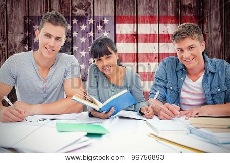 Students doing work together as they all look into the camera against composite image of usa national flag