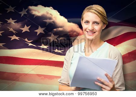 Smiling teacher against composite image of digitally generated american flag rippling
