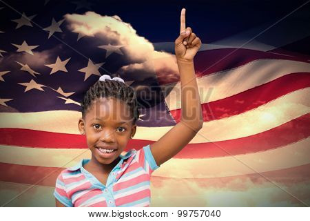 Smiling pupil with hand up against composite image of digitally generated american flag rippling