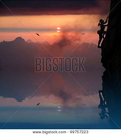 Female rock climber and mountain sunset