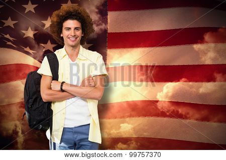 Young man with arms crossed in office corridor against composite image of digitally generated united states national flag