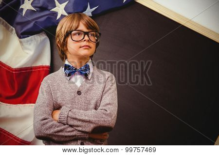 Cute pupil dressed up as teacher against american flag on chalkboard