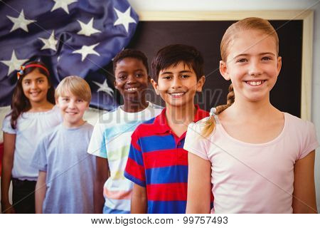 Smiling little school kids in school corridor against american flag on chalkboard