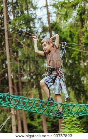 Boy climbing in adventure rope park