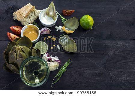 Artichokes With Dips, Garlic, Tomatoes, Lemon, Bread And Wine On Dark Wood