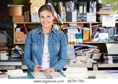 Portrait of confident female worker holding cutter at table in factory