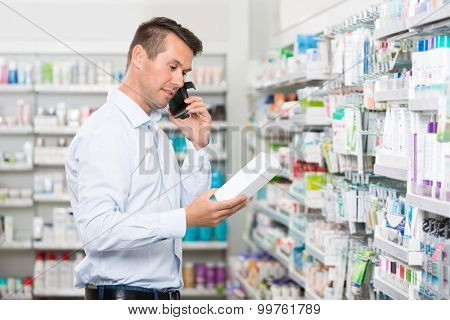 Mid adult male customer using mobile phone while holding product in pharmacy
