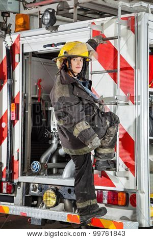 Full length of young firewoman looking away while standing on truck at fire station