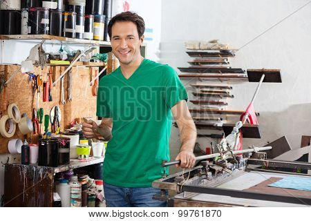 Portrait of smiling man holding brush in paper factory