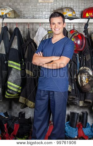Portrait of happy firefighter standing arms crossed at fire station