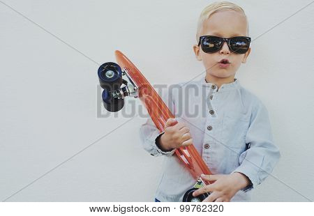 Cute Hipster Little Boy With A Skateboard
