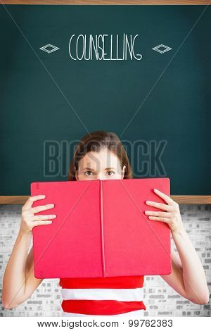 The word counselling and student holding book over face against teal