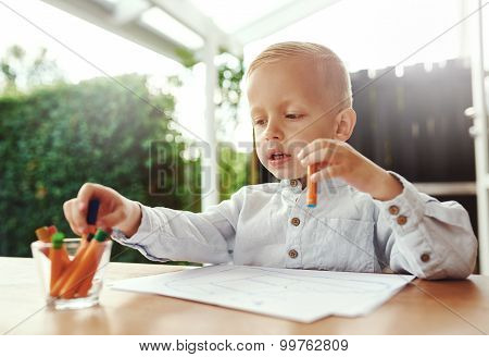 Cute Little Blond Boy Selecting A Crayon