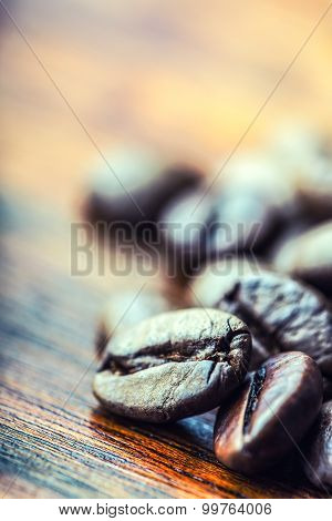 Roasted coffee beans spilled freely on a wooden table.