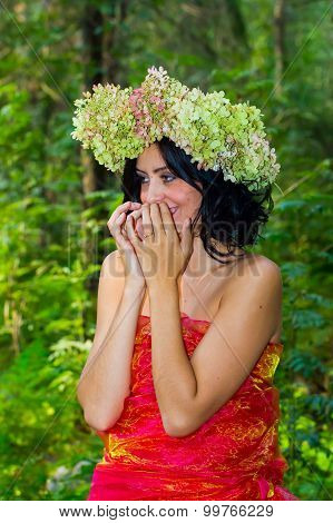 Young Russian Woman On Her Head A Wreath Of Flowers Hydrangeas, A Woman Relaxed, Reclining On A Tree