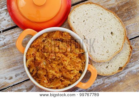 Polish bigos in saucepan and slices of home made bread on rustic wooden surface