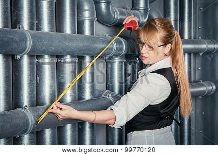 woman measuring pipes distance
