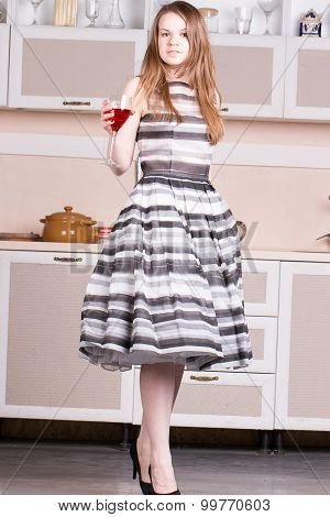 Attractive young woman dress holding a glass of wine in her kitchen.