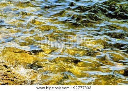 Beautiful gold to fading green waters with soft ripples on surface