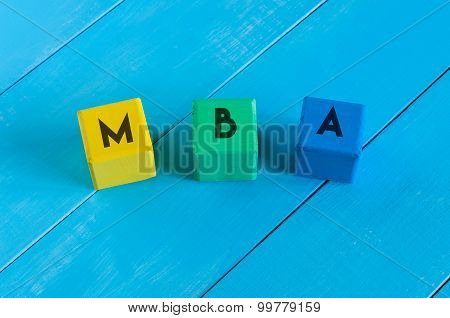 MBA or Master of Business Administration on children's colourful cubes with blue wooden background