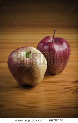 Two apples on wooden desk