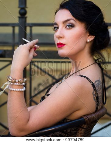 Woman Sitting In A Street Cafe And Smoking Cigarette.