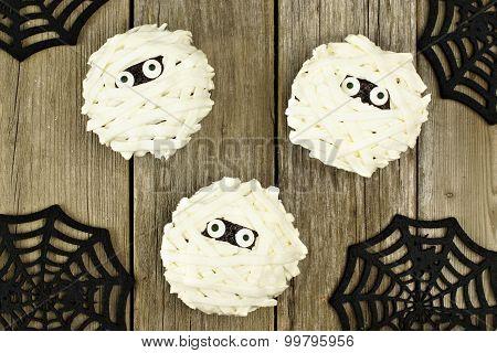 Halloween mummy cupcakes over wood