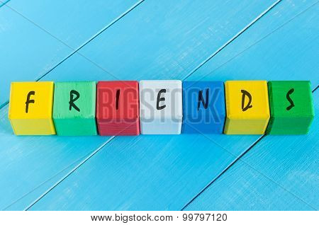 Friends - word on children's colourful cubes or blocks. Colourful wooden background