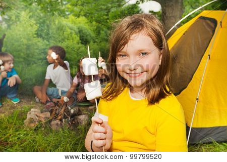 Close-up of girl holding stick with marshmallows